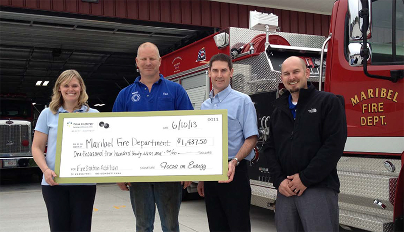 Courtney Wojcik, energy advisor from Focus On Energy, presents an energy incentive to Paul Rabas and Rick Johnson of Maribel Fire Department and Chris Herzog of A.C.E. Building Service.